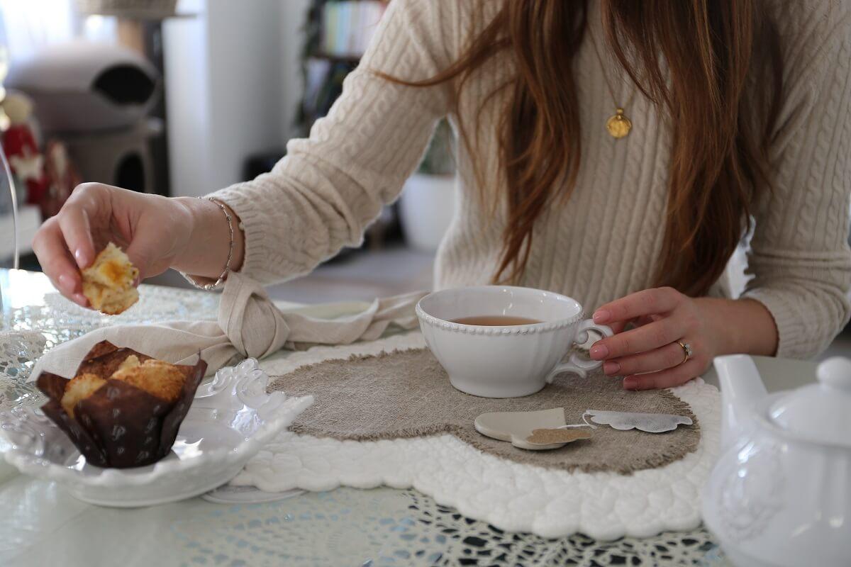 ragazza con pezzo di muffin e tazza da tè